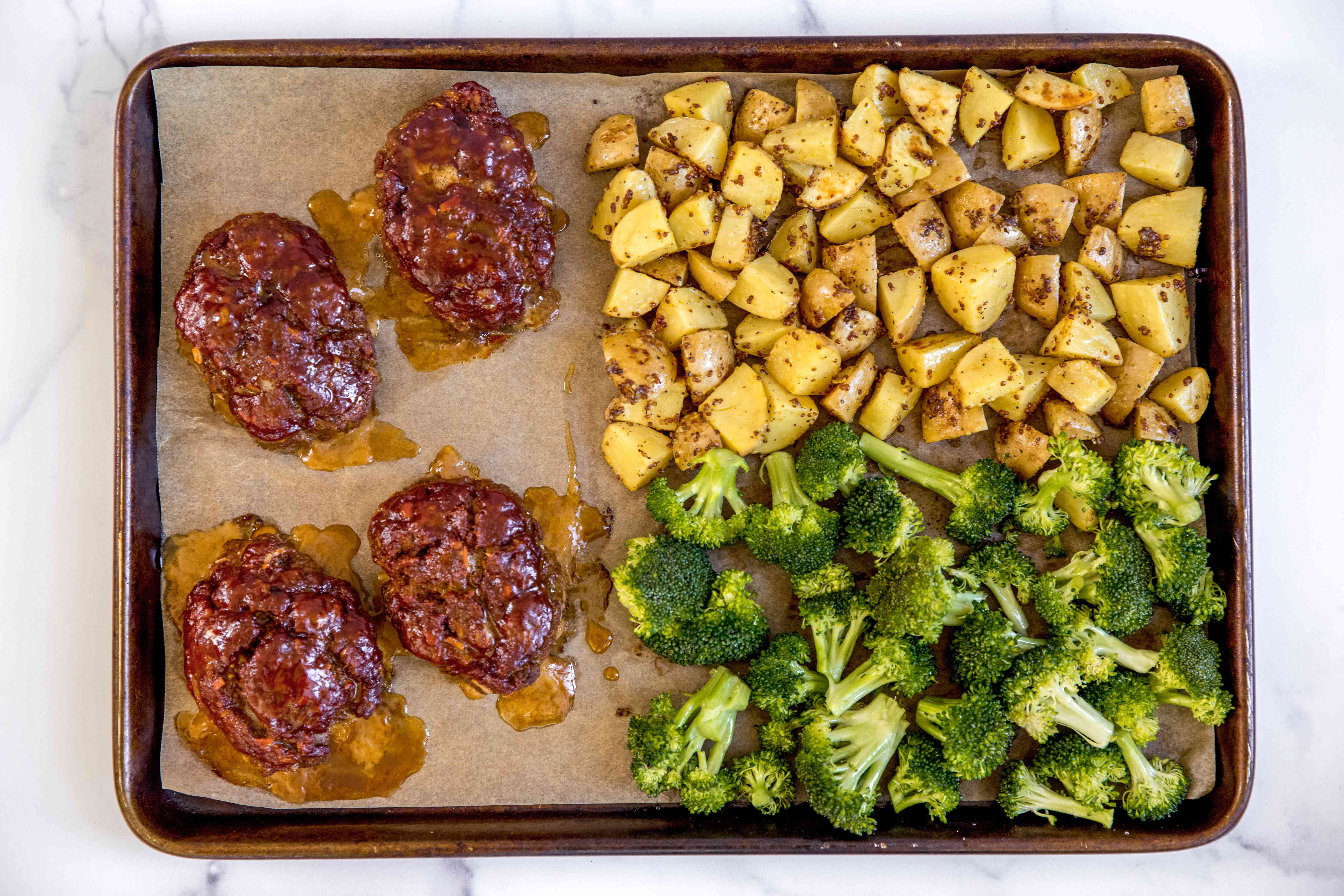 Overhead view of a sheet pan of mini meatloaves with veg and potatoes in a sheet pan.