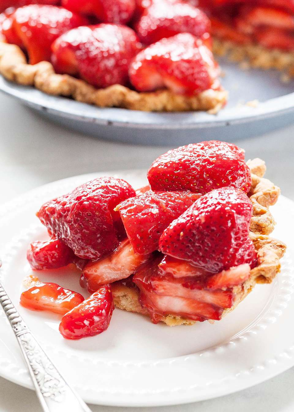 A slice of easy Strawberry Pie on a plate with the rest of the pie in the background