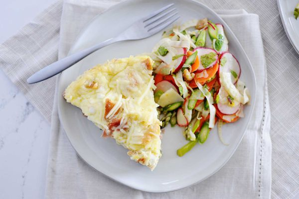 A slice of breakfast strata is on a white plate and spring salad is on the plate to the right. Sliced radish and chopped asparagus are visible in the salad. A fork is resting on the top of the plate. Cream linens are under the plate.