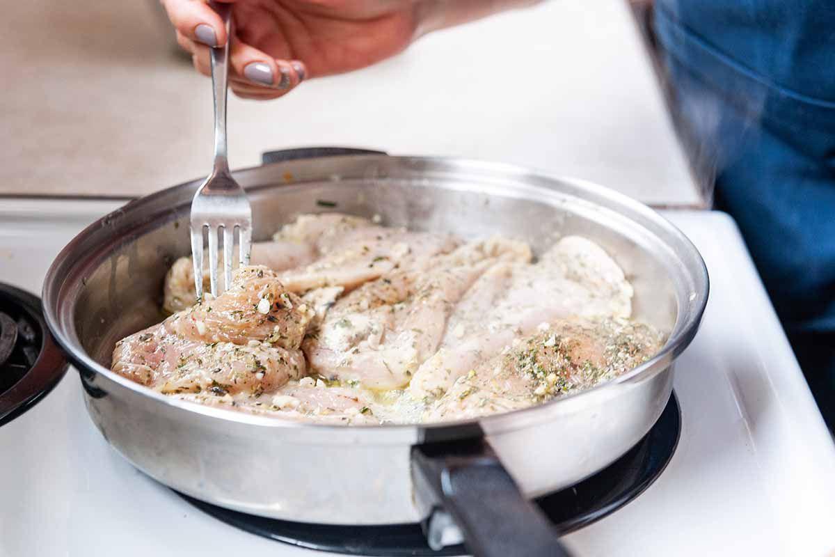 Chicken Freezer Meal with Chicken Tenders-fork flipping chicken tenders in skillet