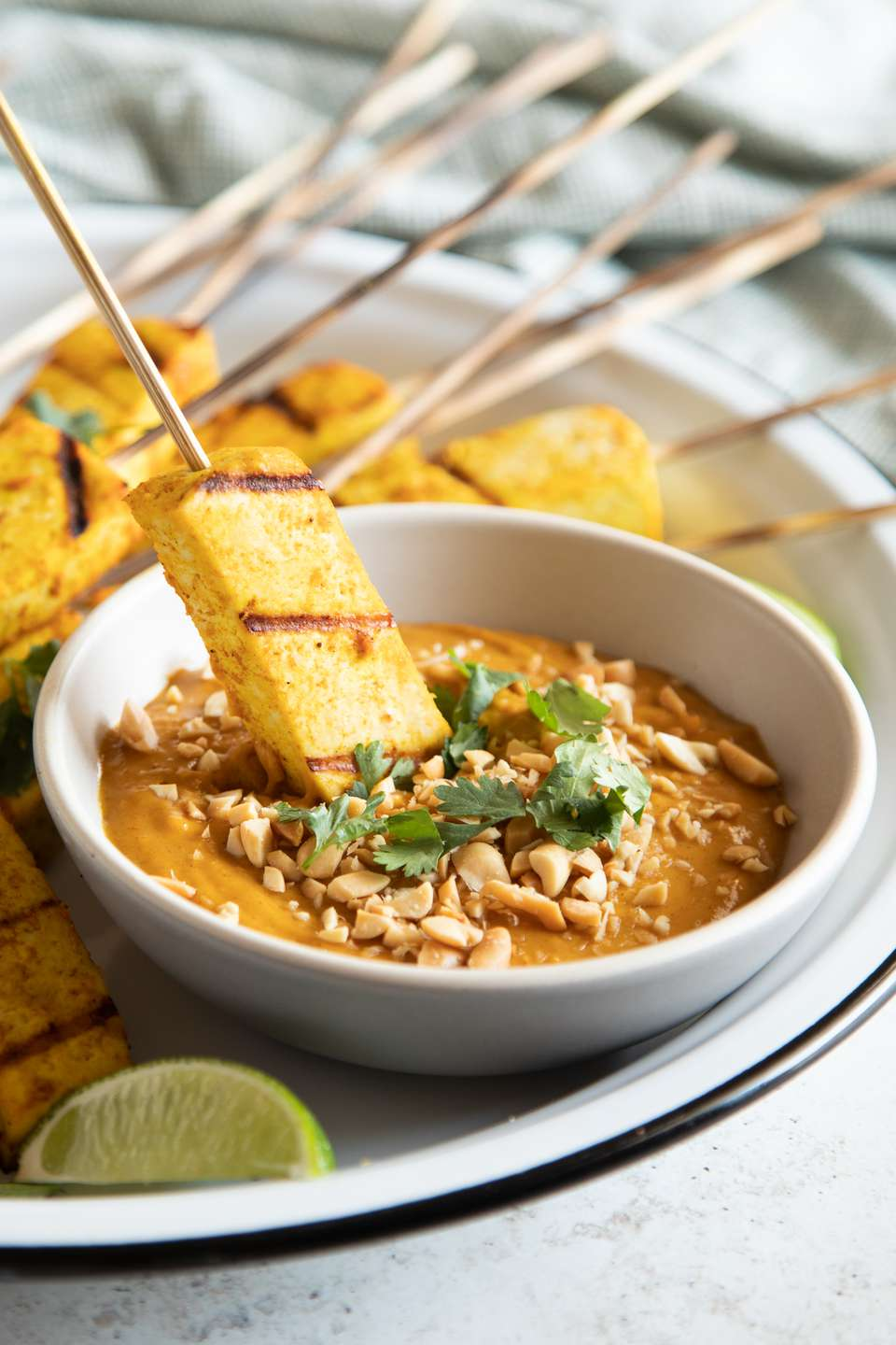 Grilled tofu skewers with spicy peanut sauce with one skewer dipped in sauce.