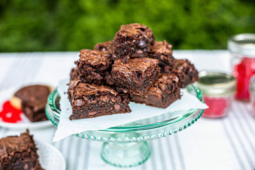 Brownies stacked on a cake stand set outside for things to do with your family.