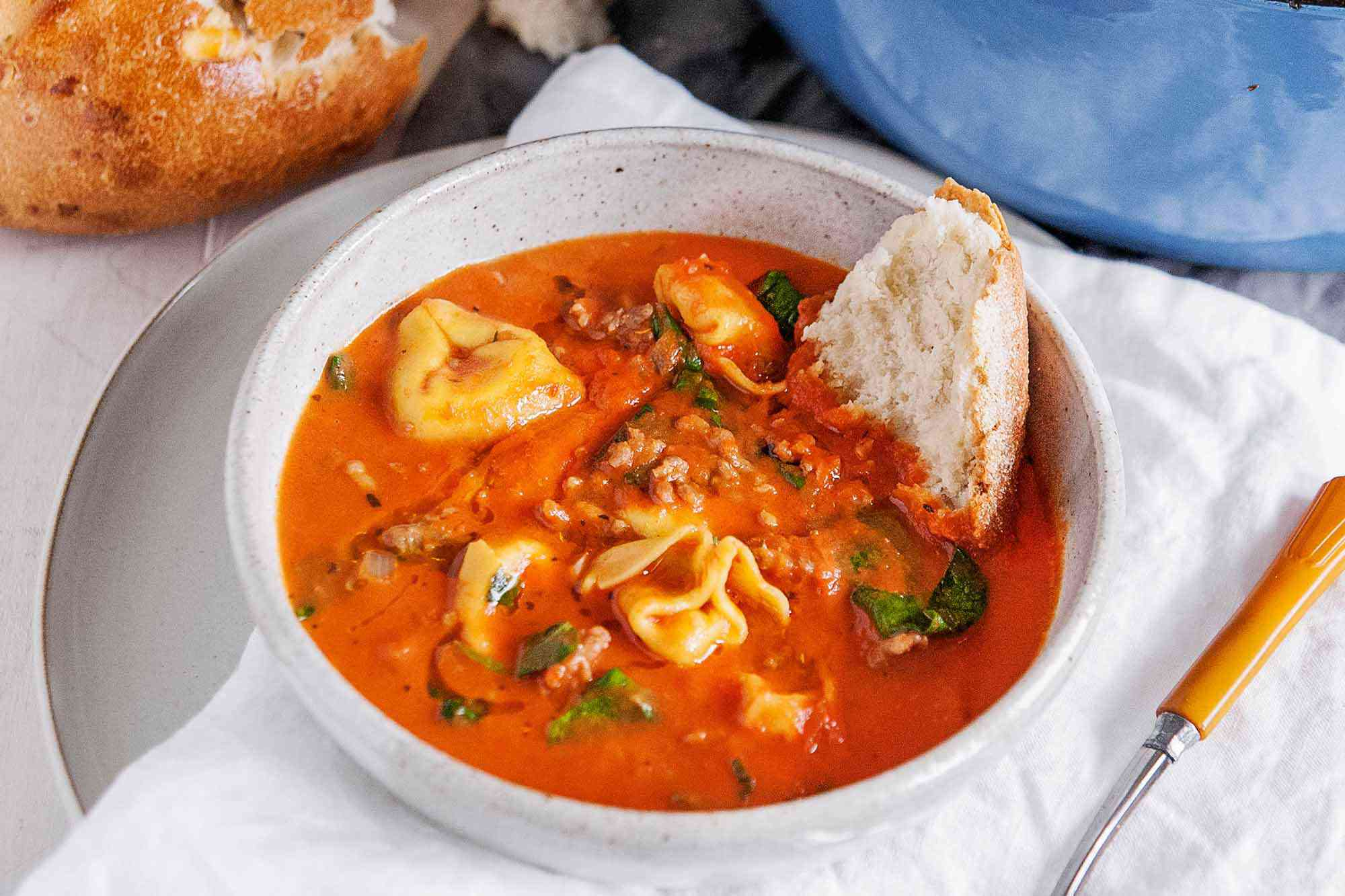Italian Sausage Tortellini Soup - white bowl with tomato soup, fresh basil and cheese filled tortellini wtih a blue pot in the background