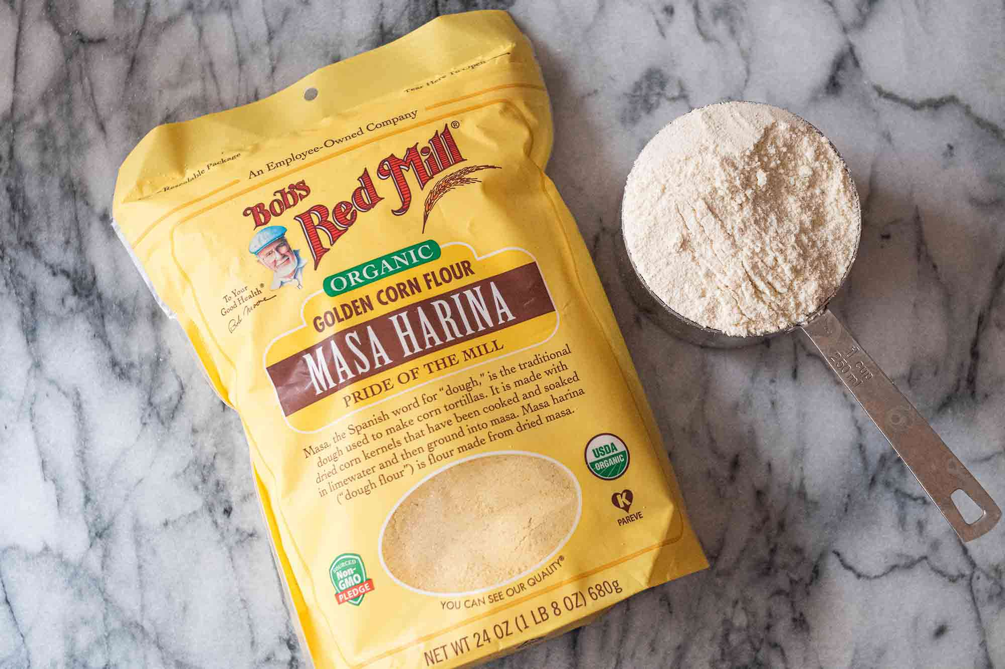 Bob's Red Mill Masa Harina on a marble backdrop with a measuring cup filled with the corn flour.