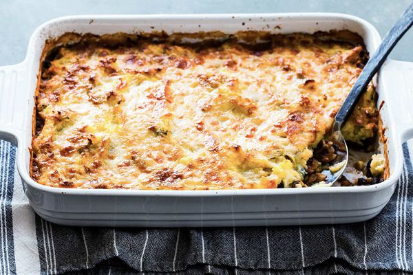 Horizontal view of easy shepherd's pie with a striped dish towel underneath white casserole dish. Serving spoon insdie with a scoop missing.