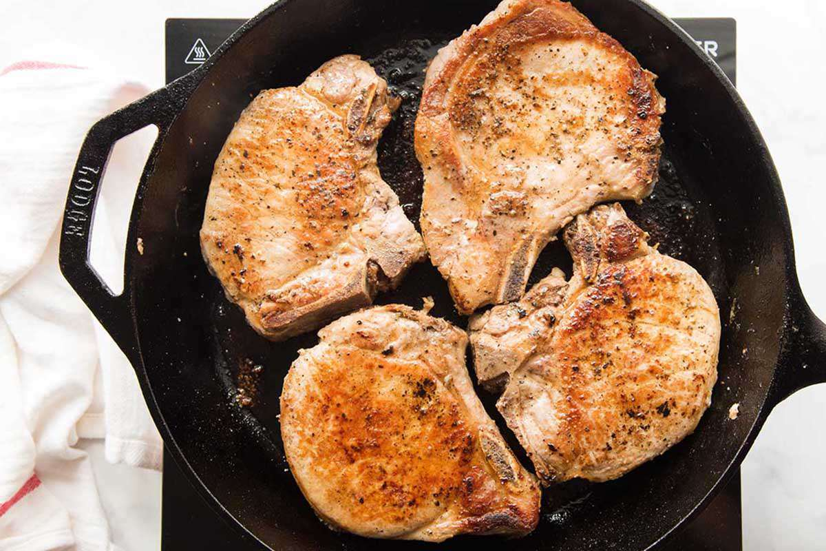 Pork chops browned in a cast iron skillet with a hand sprinkling salt and pepper over the chops.