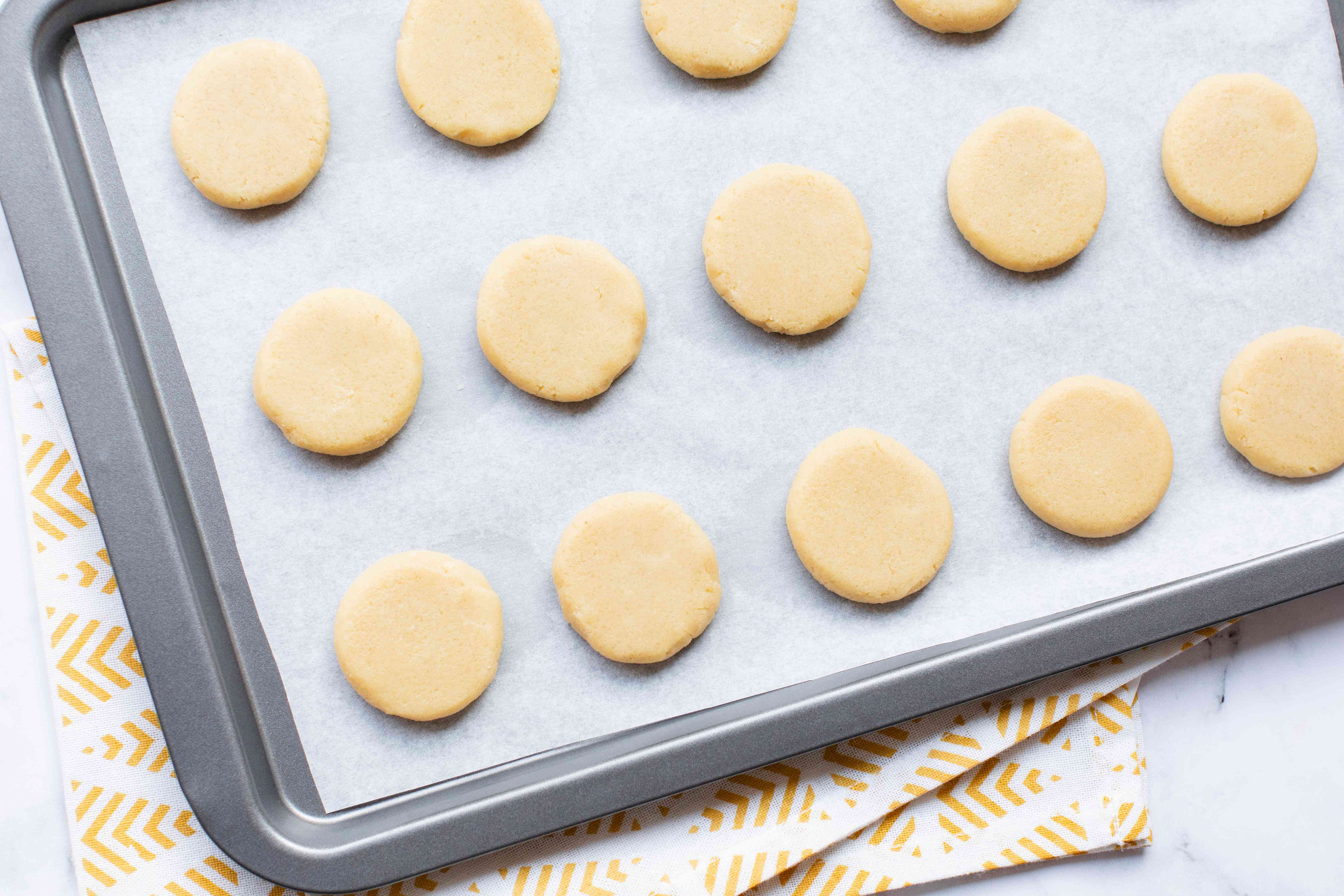 Flattened dough balls on a baking sheet for a Chinese almond cookie recipe.