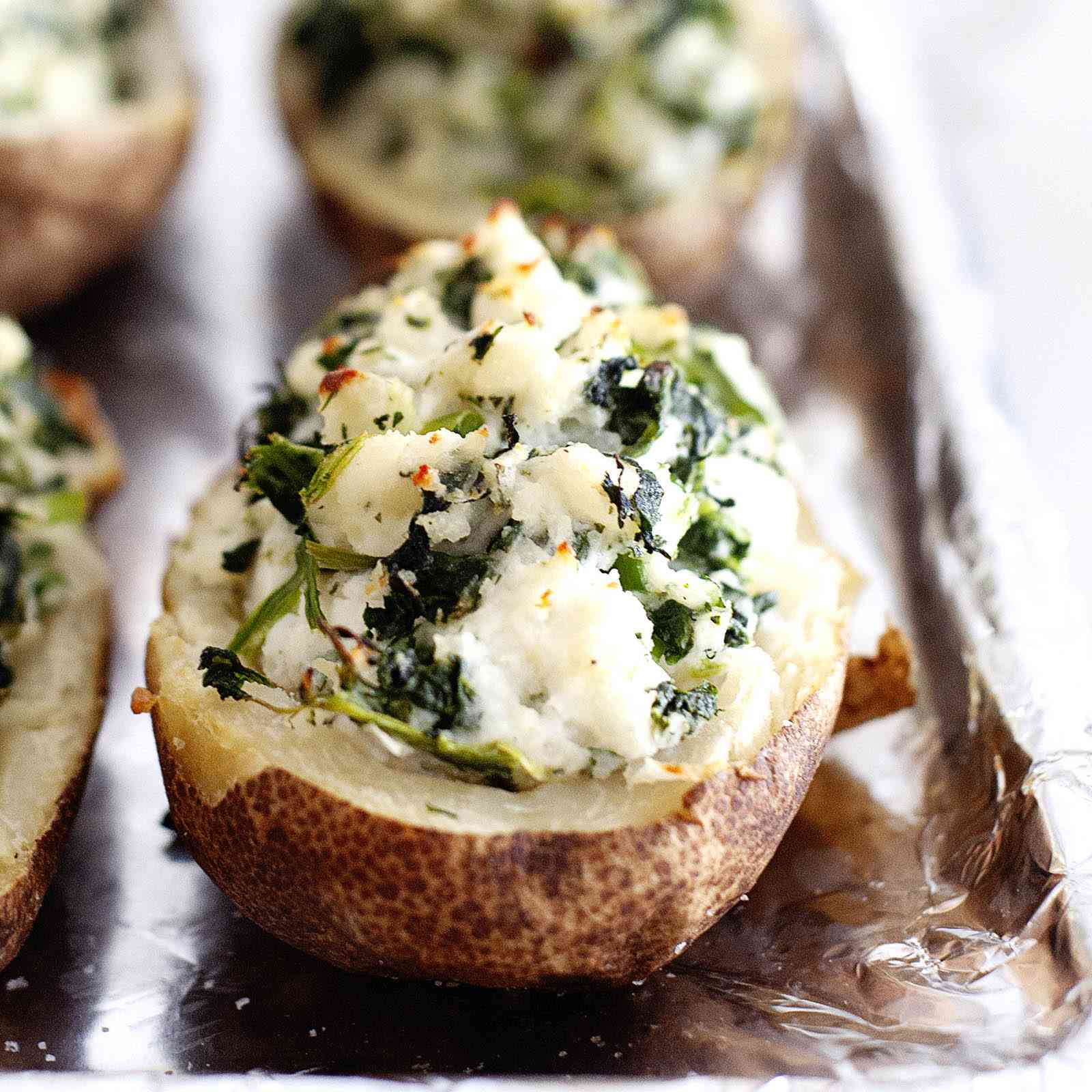 Close up of twice baked potatoes stuffed with spinach and feta on an aluminum foil-lined baking sheet.