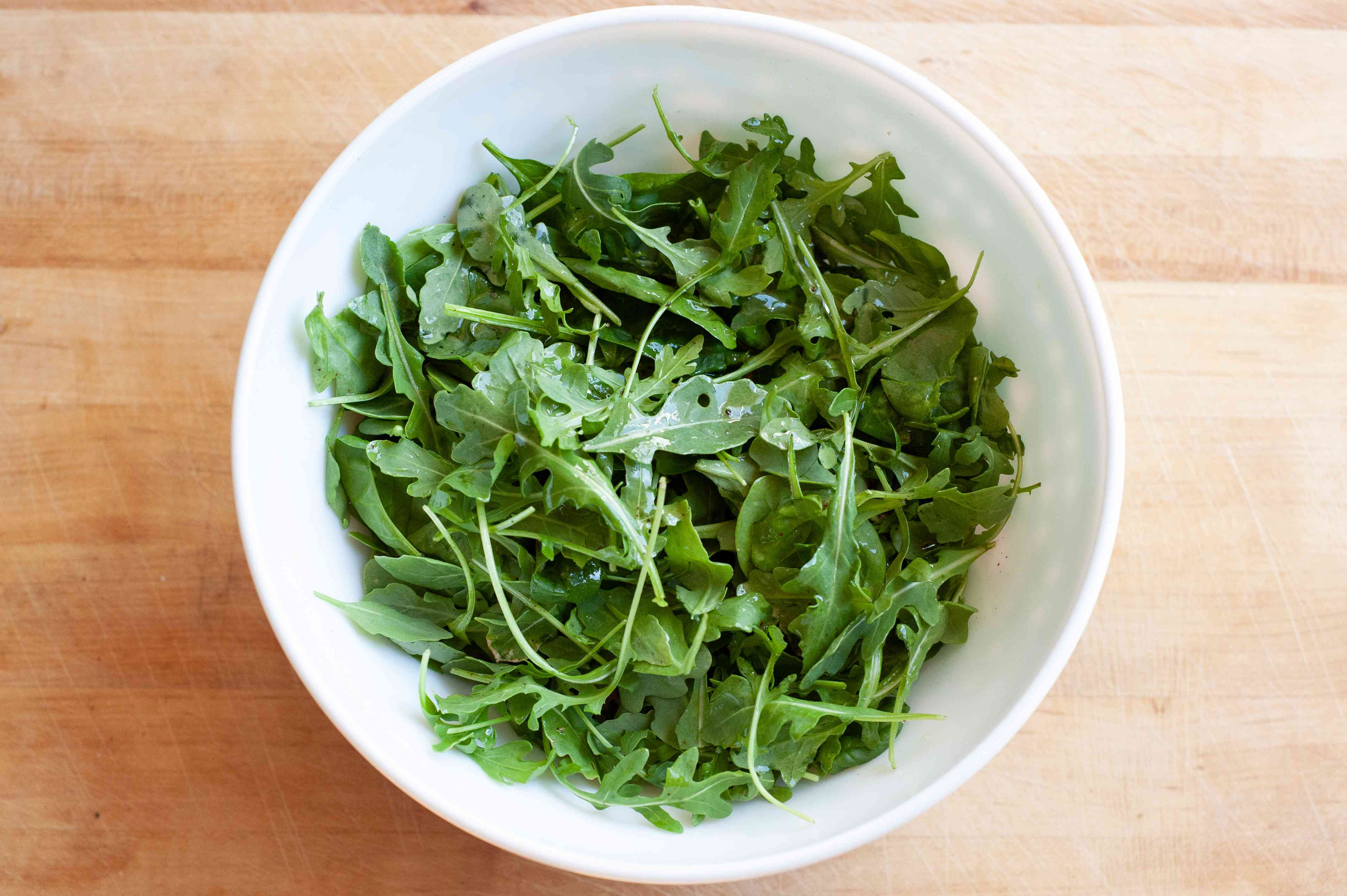 A bowl of arugula for pasta with bacon and tomatoes.