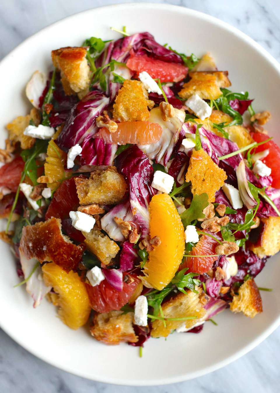 Citrus Salad on a white plate. Supremed orange and grapefruit, radicchio, croutons and feta cheese crumbles are visible.