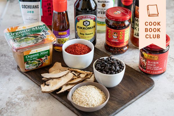 Asian pantry essentials miso soy sauce kimchi on a wood cutting board