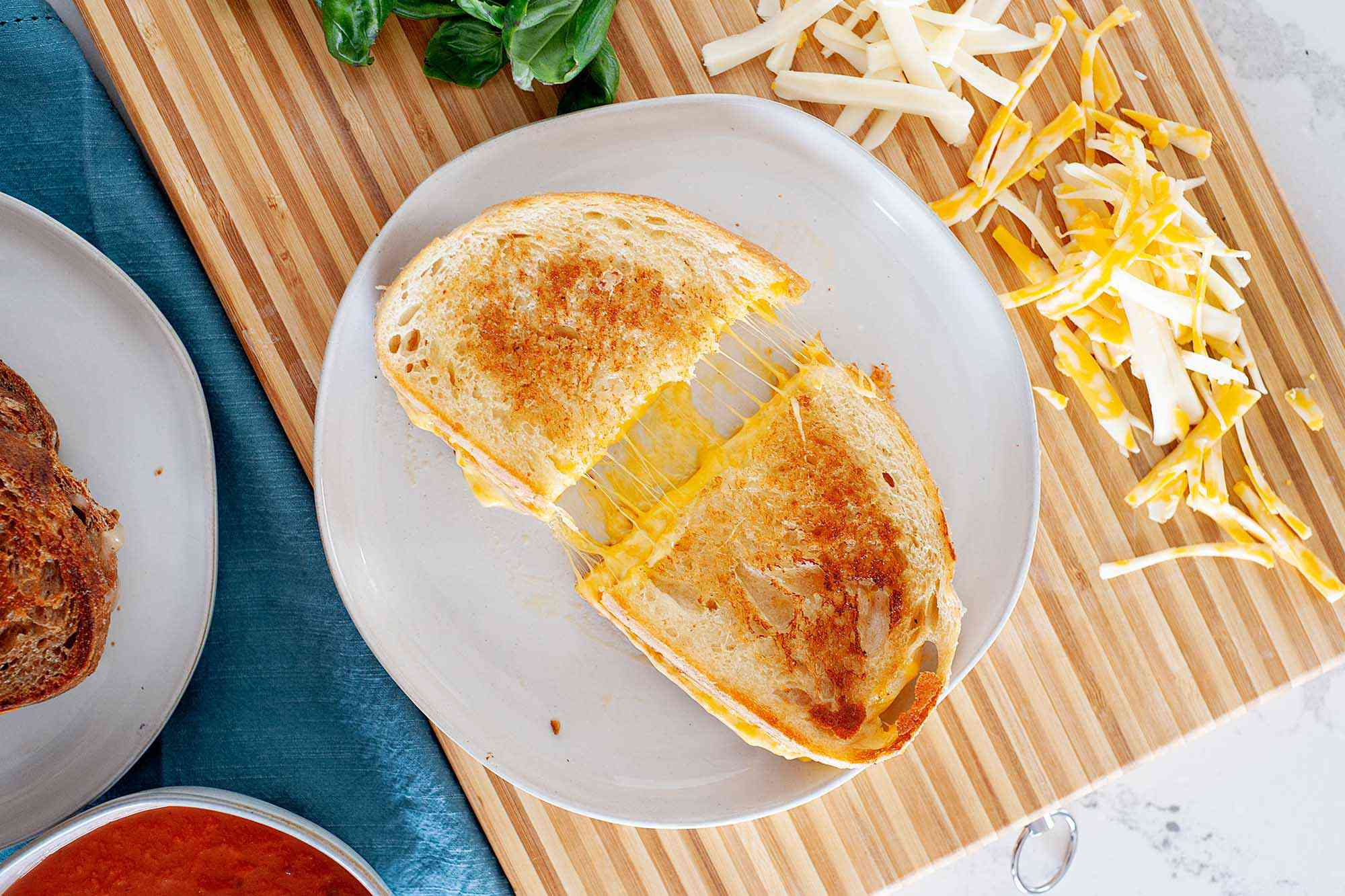 A grilled cheese sandwich cut in half on a plate with the cheese stretched between the two halves in oooey gooey goodness. There are shredded cheese bits strewn about and basil leaves on a cutting board nearby.