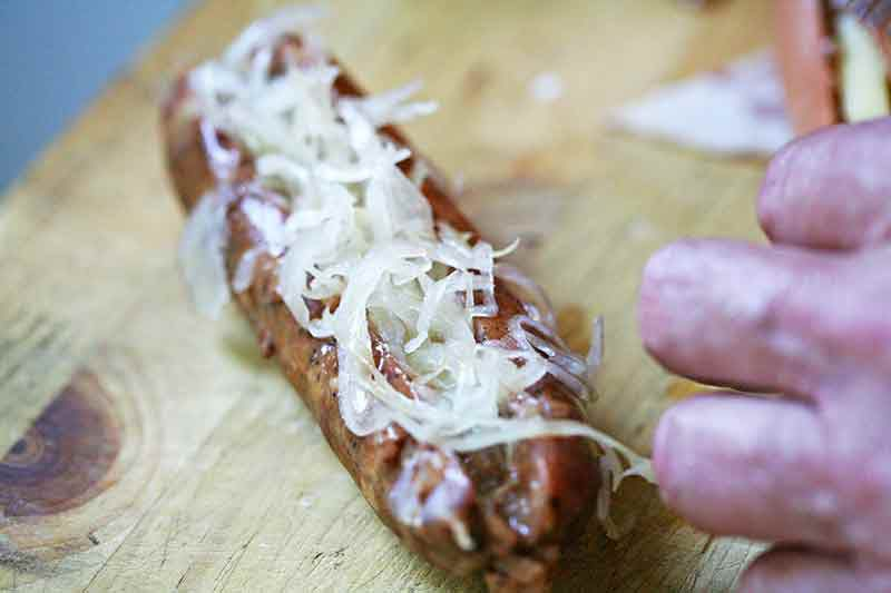 Stuffing hot dog with sauerkraut for bacon wrapped hot dogs