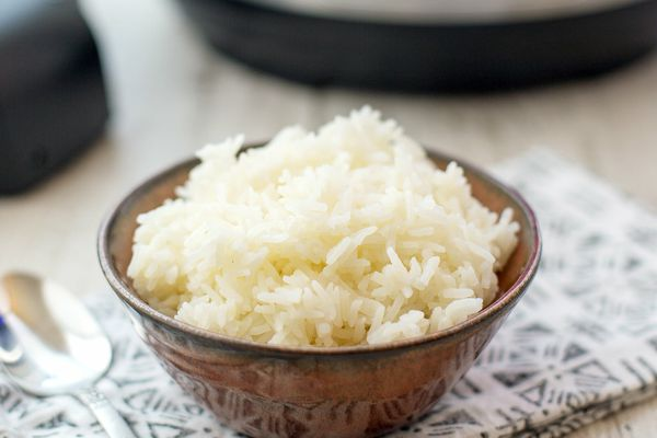 Instant Pot rice in a bowl with a spoon and the instant pot in the background