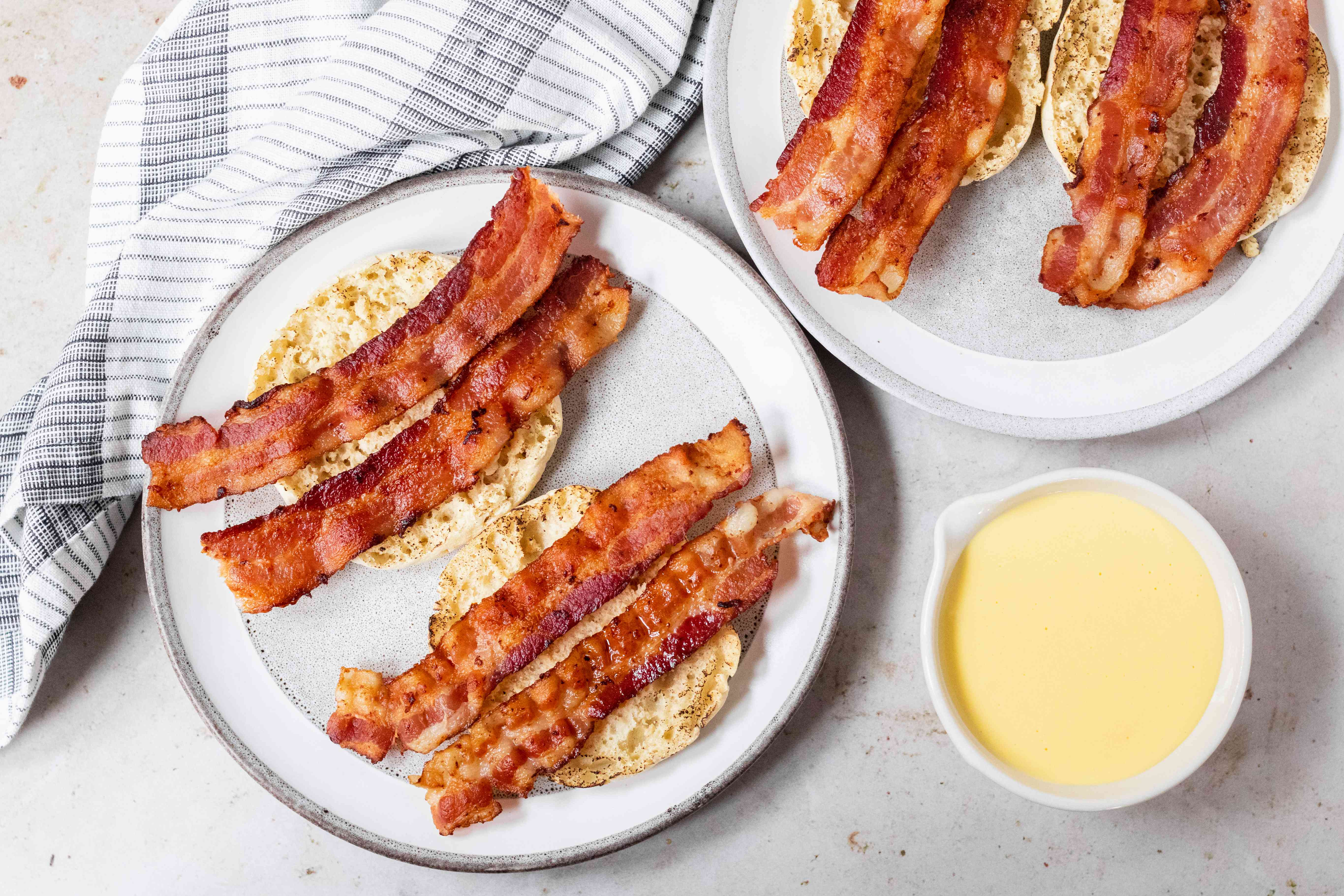 English muffins topped with bacon with hollandaise sauce on the side to show how to make eggs benedict.
