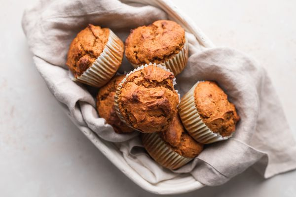 Classic pumpkin muffins nestled in a cream colored linen and oval bowl.