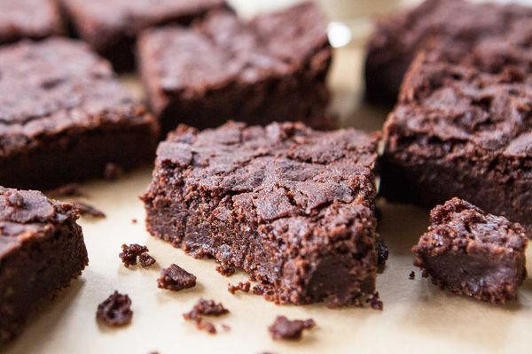 Fudgy Gluten-Free Vegan Brownies on a surface with one brownie cut in half