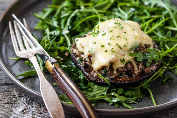 How to Make Stuffed Mushrooms - mushroom with melted cheese on top sitting on a bed of greens.