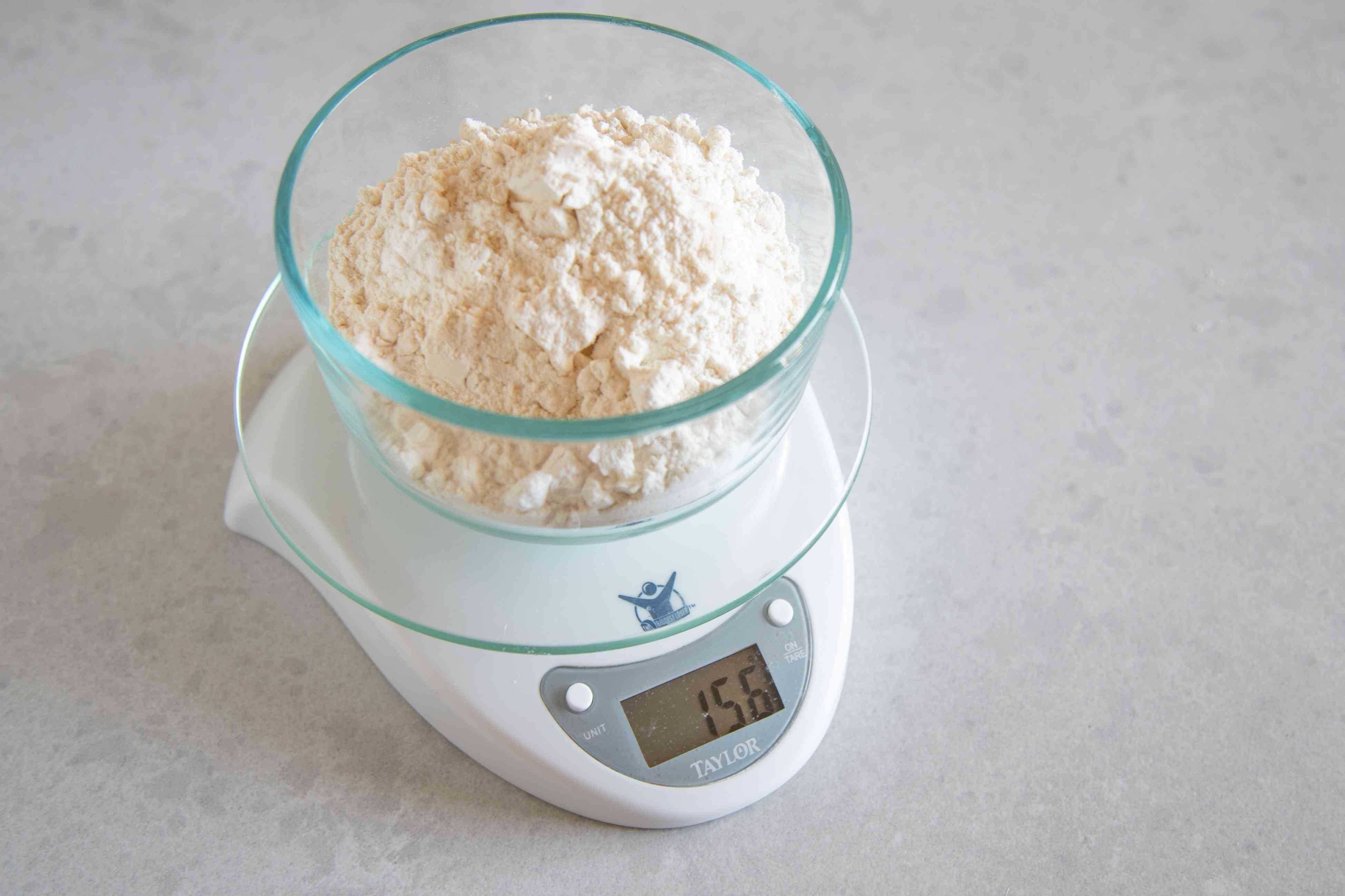 A glass bowl on a kitchen scale to show the best way to measure flour.