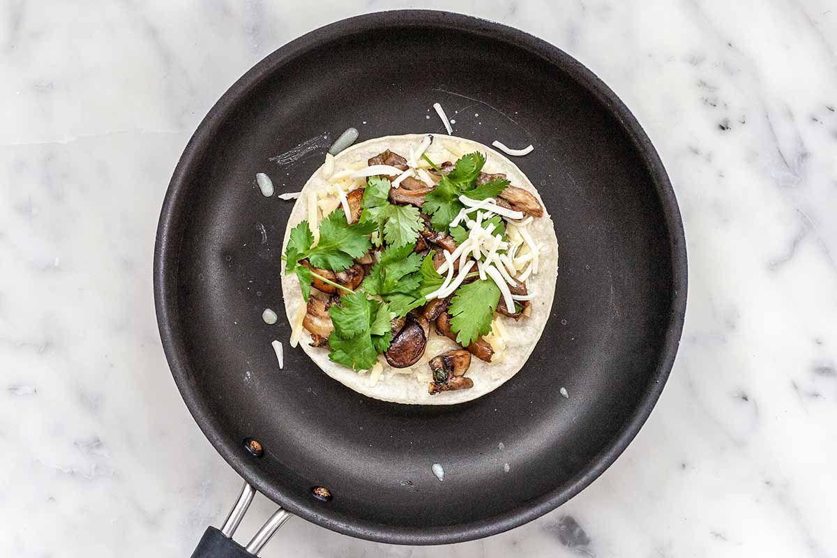 Cheese Quesadilla with Mushrooms - black skillet with quesadilla filled with cilantro, mushrooms and cheese.