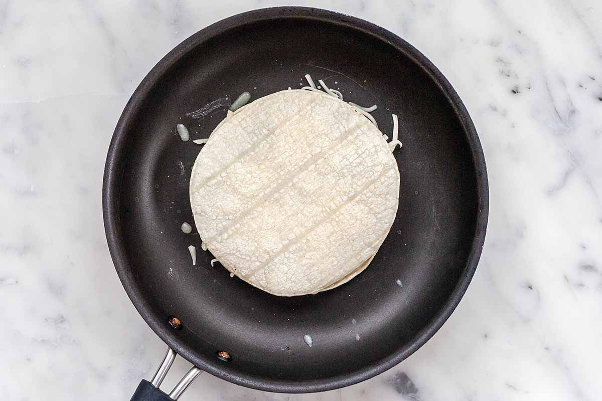 How to Make a Cheese Quesadilla with Mushrooms - uncooked tortillas filled iwth cheese in mushrooms in black skillet