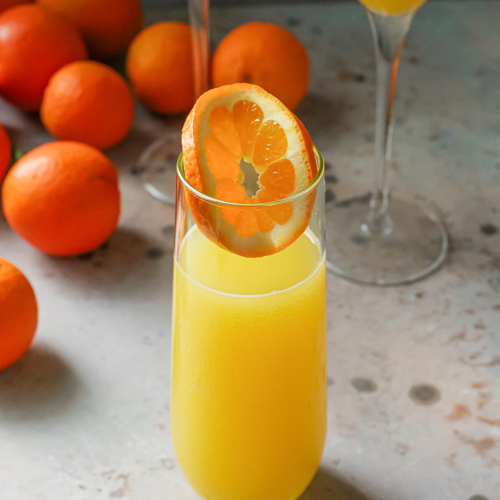 Eeasy mimosa in a glass with an orange slice inside. Two flutes of mimosa are behind the glass and oranges are behind the drinks.