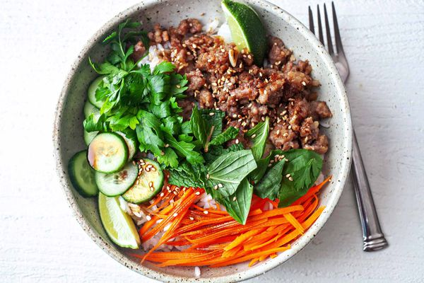 Pork Rice Bowl Recipe herbs in center of bowl with pork and carrots on side