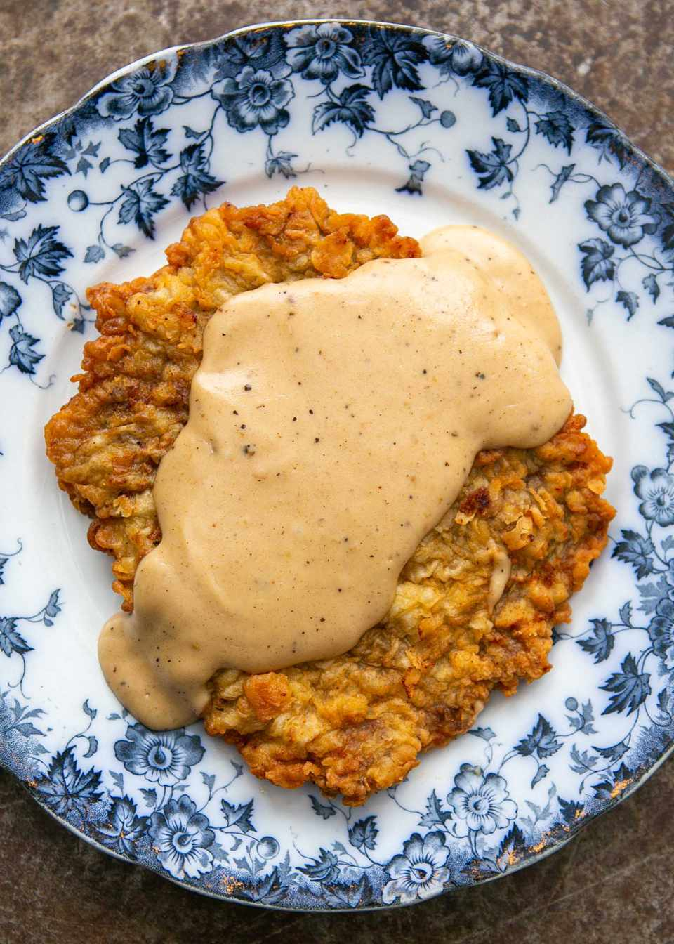Homemade country fried steak with gravy on a plate