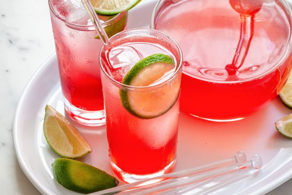 Best ever raspberry lime rickey in two glasses with a pitcher behind it.