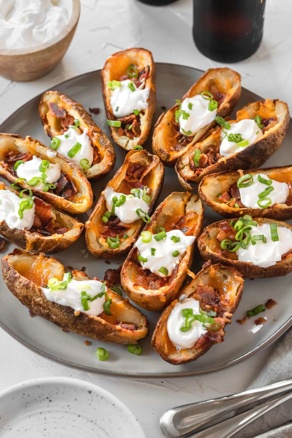 A platter of potato skins topped with cheese and sour cream.