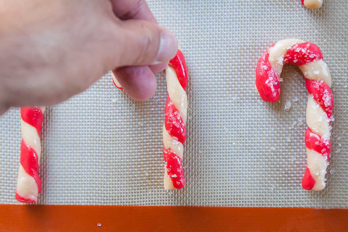 Hand Sprinkling Sugar on Candy Cane Cookies