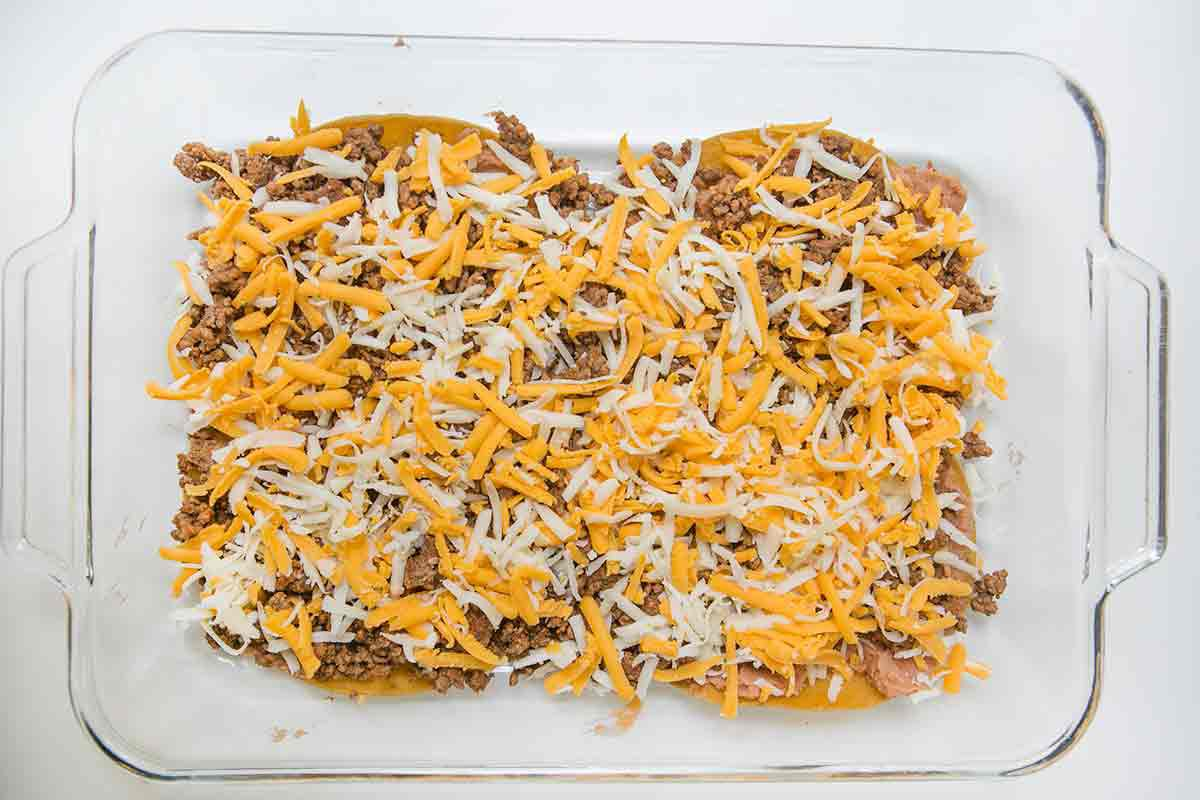 To make mexican lasagna, sprinkle grated cheese over the beef layer