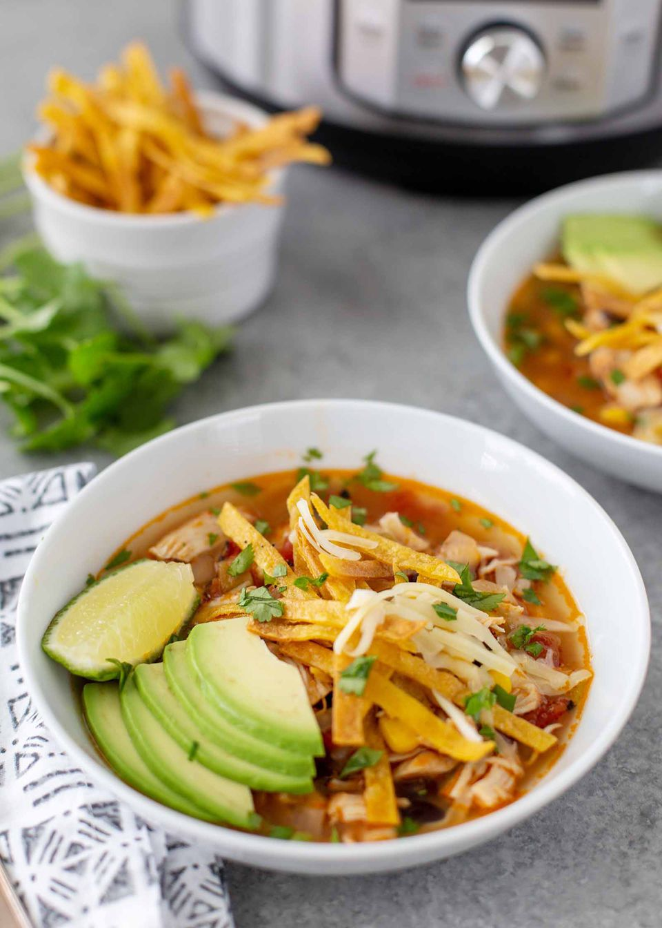 A white bowl of the best instant pot chicken tortilla soup. Each bowl has a red broth with shredded chicken, slices of fried tortilla, cheese, lime wedge and avocado slices. A couple stems of cilantro are in the bottom right corner. A ramekin has strips of fried tortillas inside and the bottom of an instant pot is visible at the top of the photo. A grey patterned linen napkin is next to the bowl. A second bowl of soup is partially visible to the right of the first bowl.