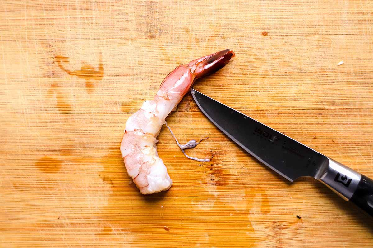 A raw shrimp is on a cutting board with a knife blade cutting the vein out of it.