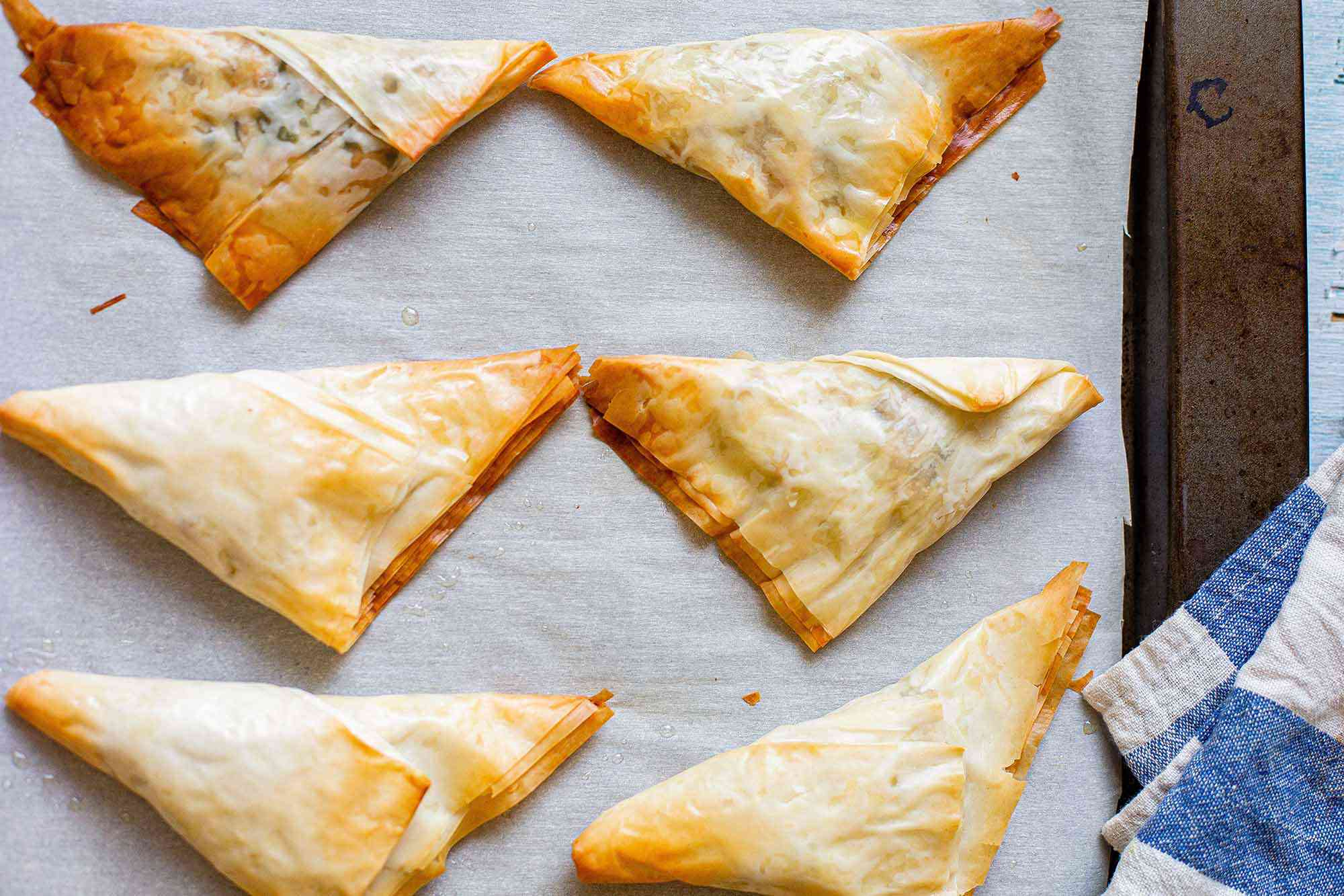 Easy Baked Indian Chicken Tikka Masala Samosa made with phyllo dough folded into a triangles on a baking sheet.