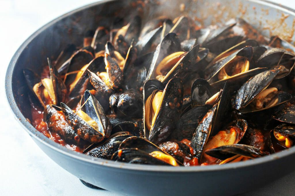 How to Cook Mussels in Tomato Sauce - closeup of steaming mussels in cast iron pan