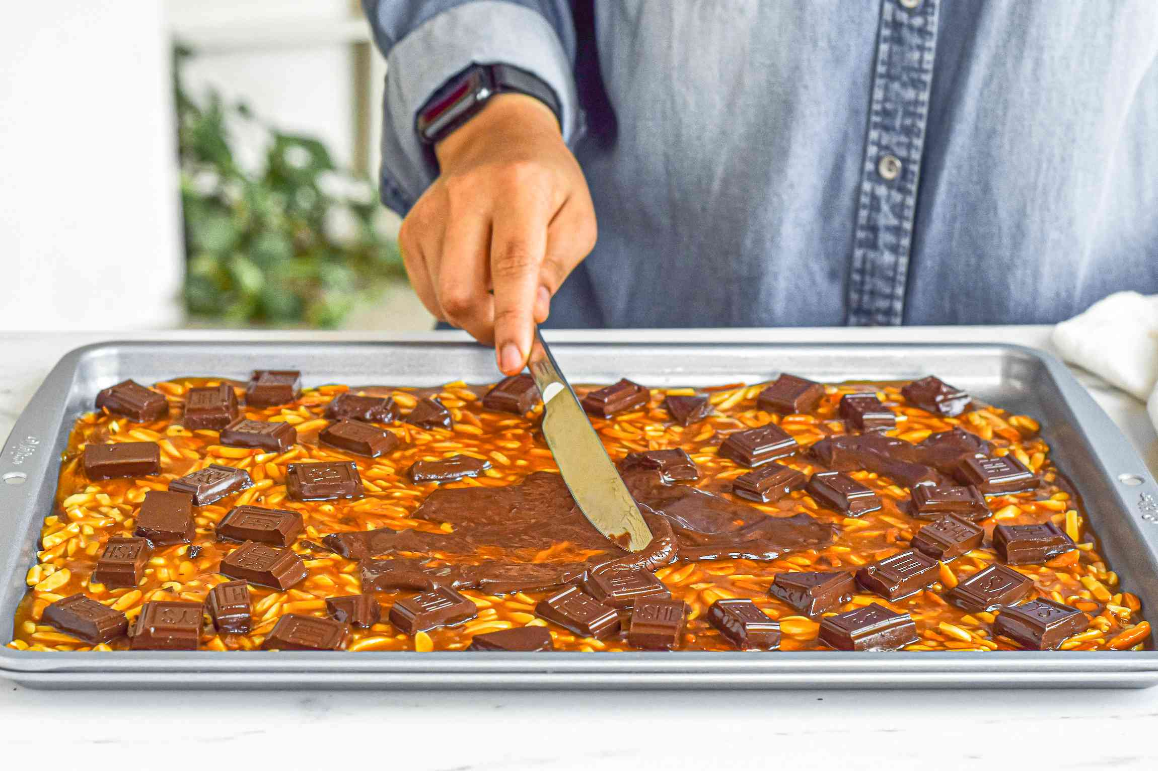 Spreading melted chocolate over almond roca.