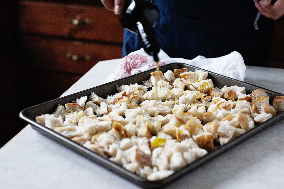 Woman drizzling olive oil on cubed bread on a baking sheet to make thanksgiving stuffing wiht apples and sausage..