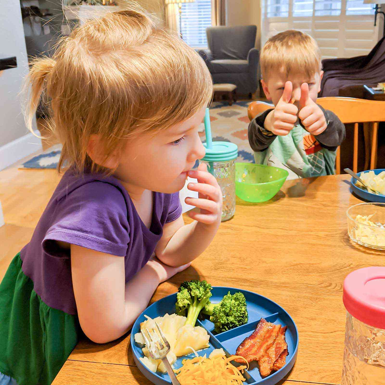 A young girl and boy are sitting at a kitchen table with plates and drinks in front of them. One plate is split into four sections. Each section has one type of food on it. Bacon, shredded cheddar cheese, mashed potato and cooked broccoli is on the plate. The boy is giving a thumbs up sign at his chair.