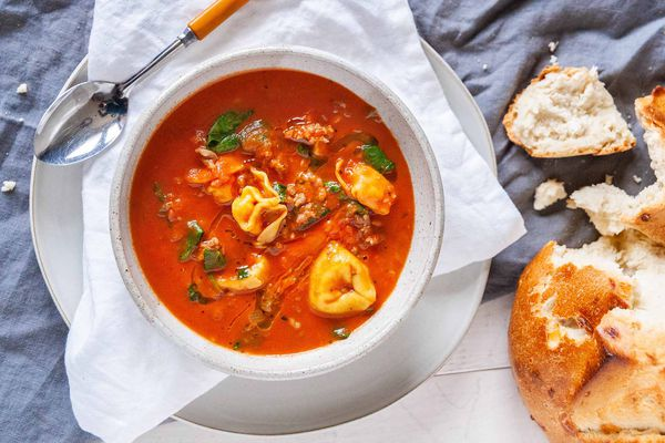Easy Tortellini Soup - white bowl with tomato soup, fresh basil and cheese filled tortellini