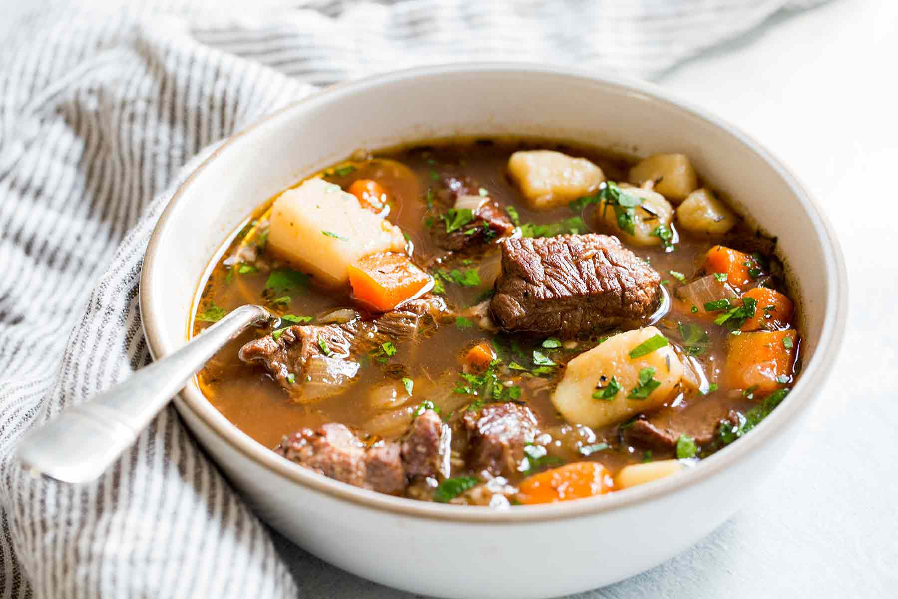 Irish stew with beef, carrots, and potatoes, Guinness and wine served in a bowl