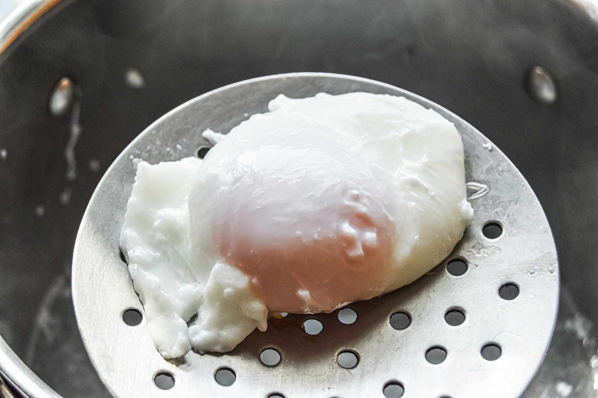 A poached egg in the bottom of a strainer.
