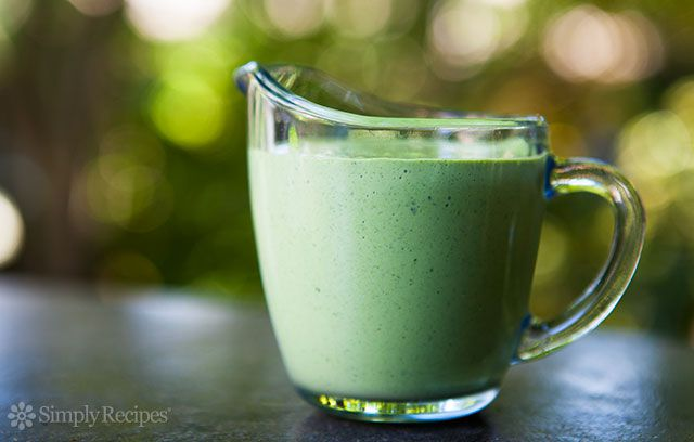 a glass pitcher filled with creamy green goddess dressing