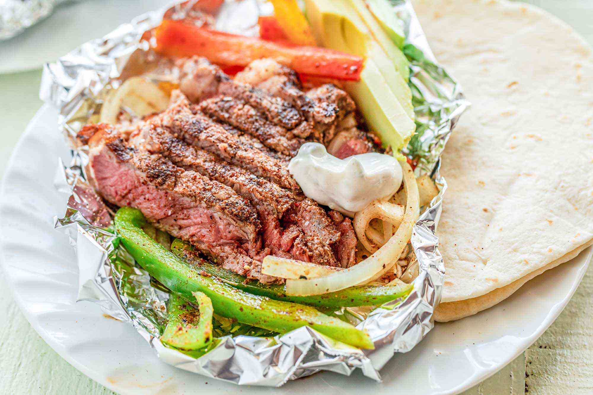 Plate with grilled steak foil packet opened up to reveal steak, peppers, onions inside. Avocado slices and sour cream are also in the packet and a flour tortilla is to the right.