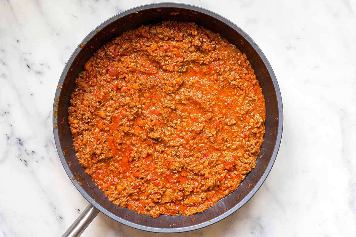 A homemade bolognese sauce in a skillet on a marble countertop