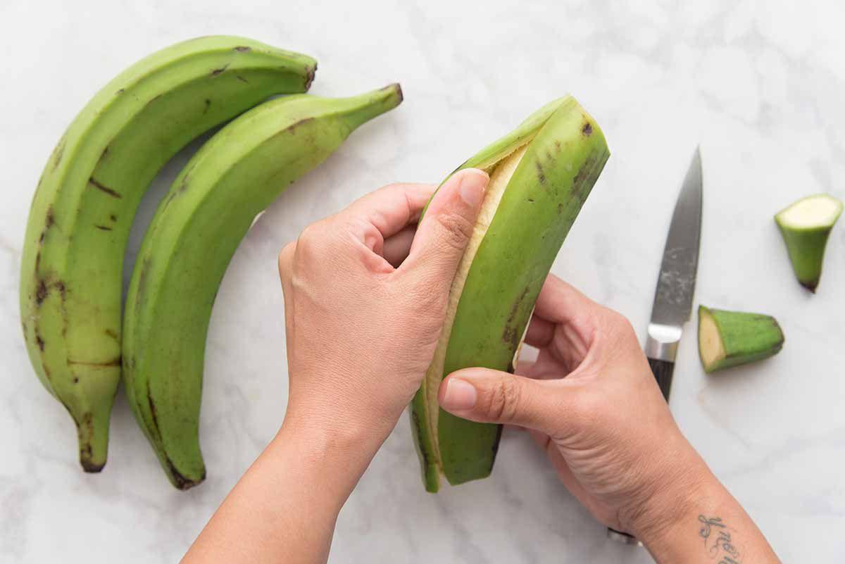 Person peeling a green plantain