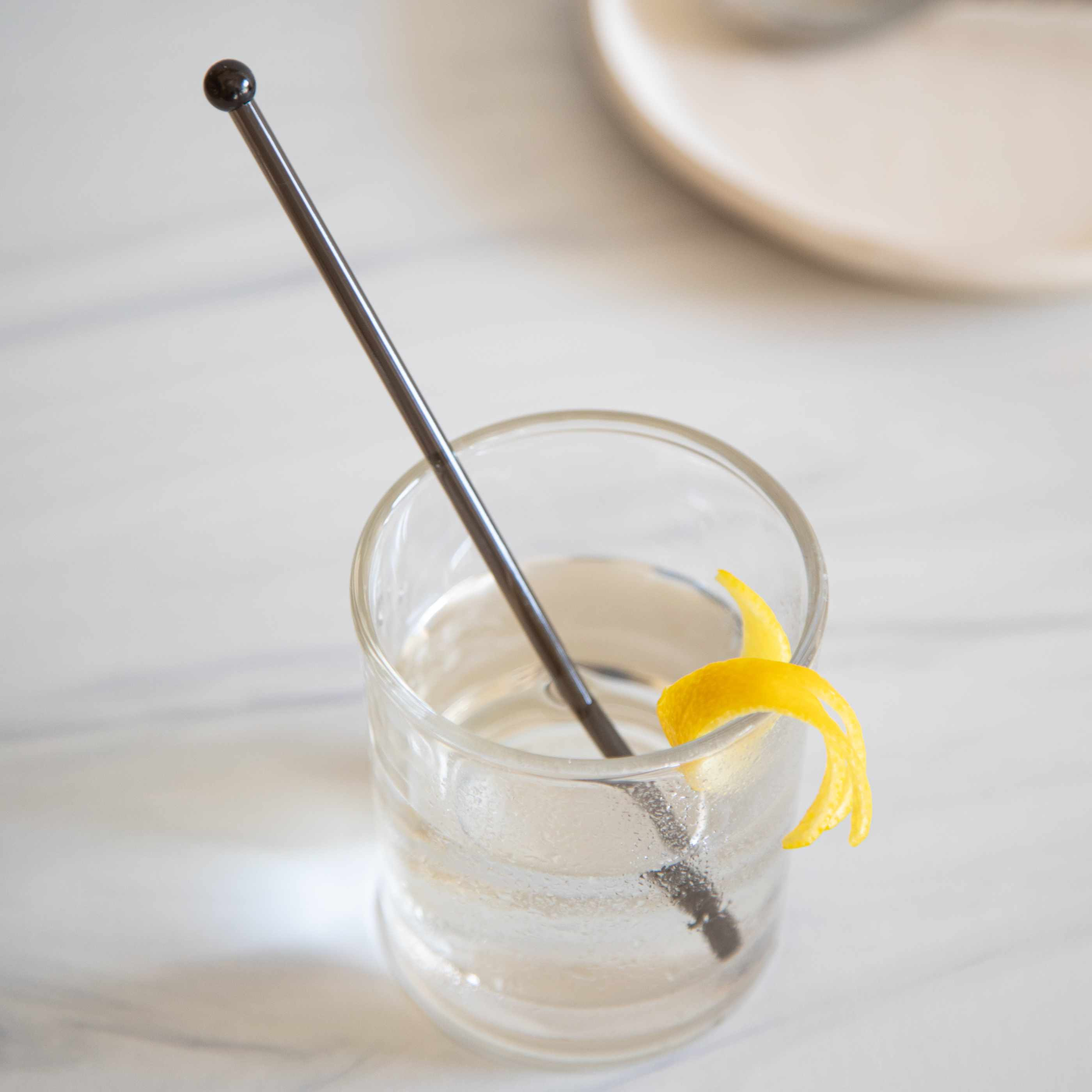 50/50 Gin Martini with a stir stick and lemon peel garnish.