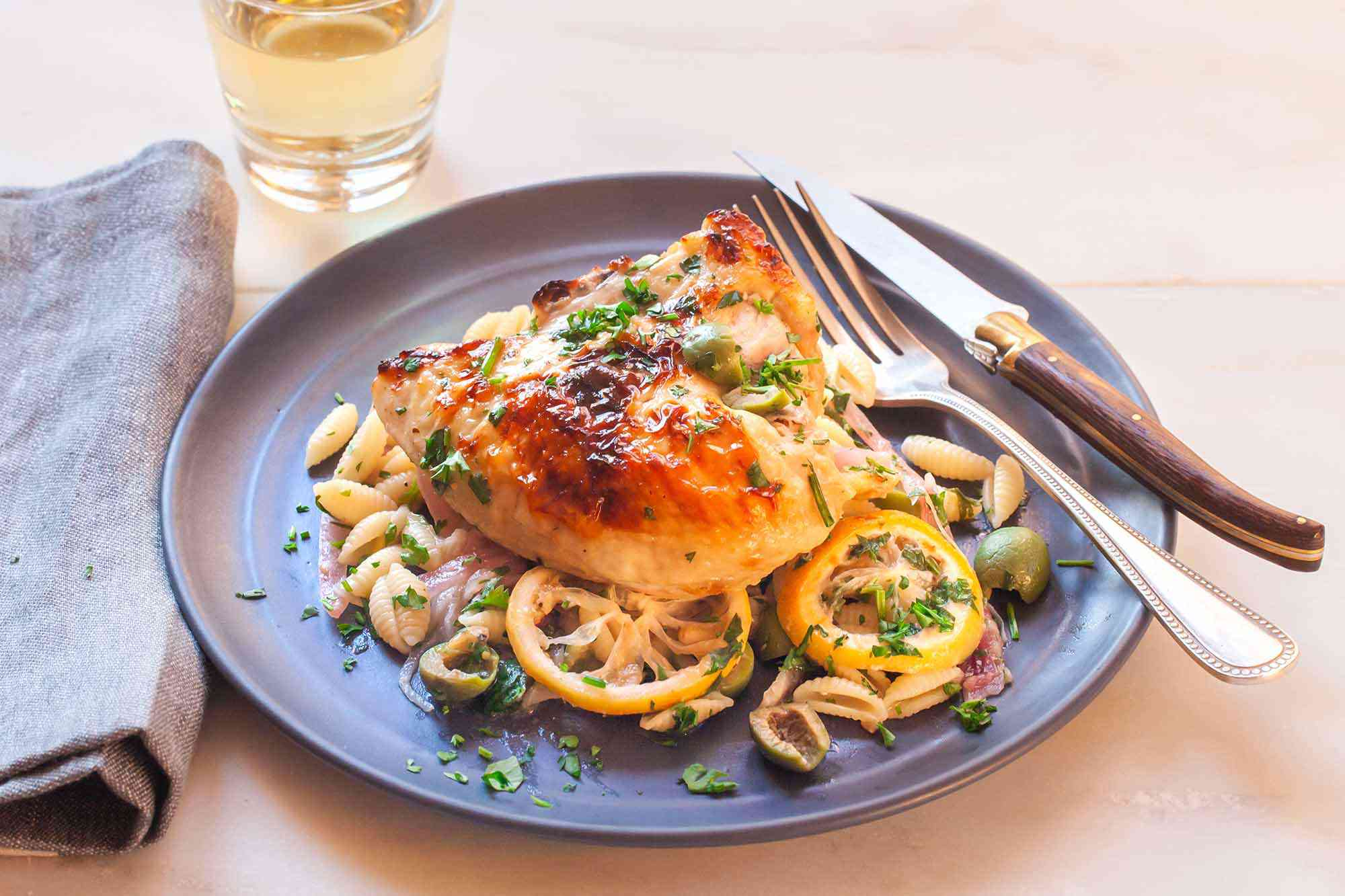 Yogurt marinated lemon chicken with pasta, olives and herbs on a rimmed plate. A fork and knife rest on the right edge of the slate plate. A grey linen is folded to the left of the plate an a tumbler of white wine is above the plate to the left.