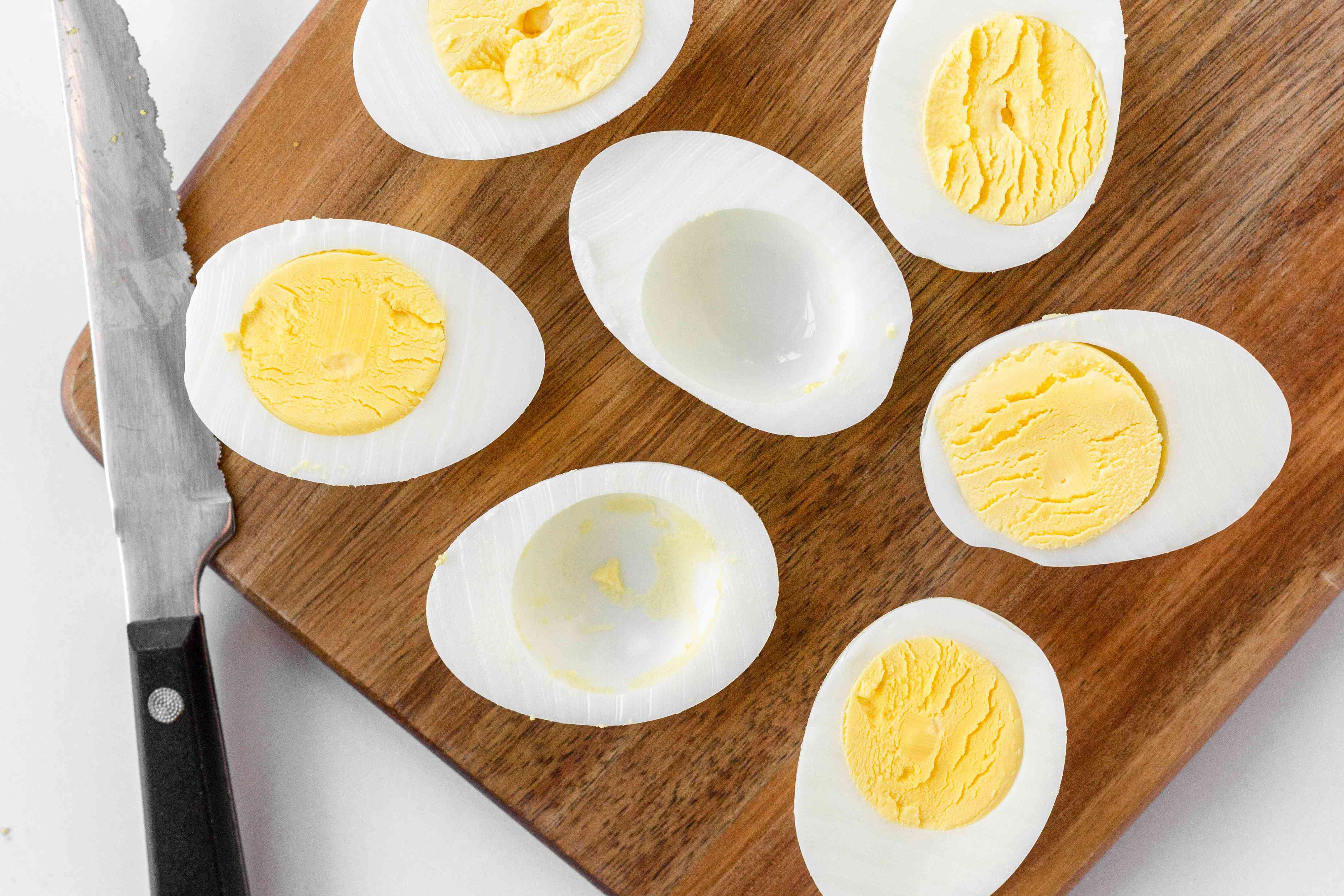 Hard boiled eggs sliced in horizontally and set on a wooden board.