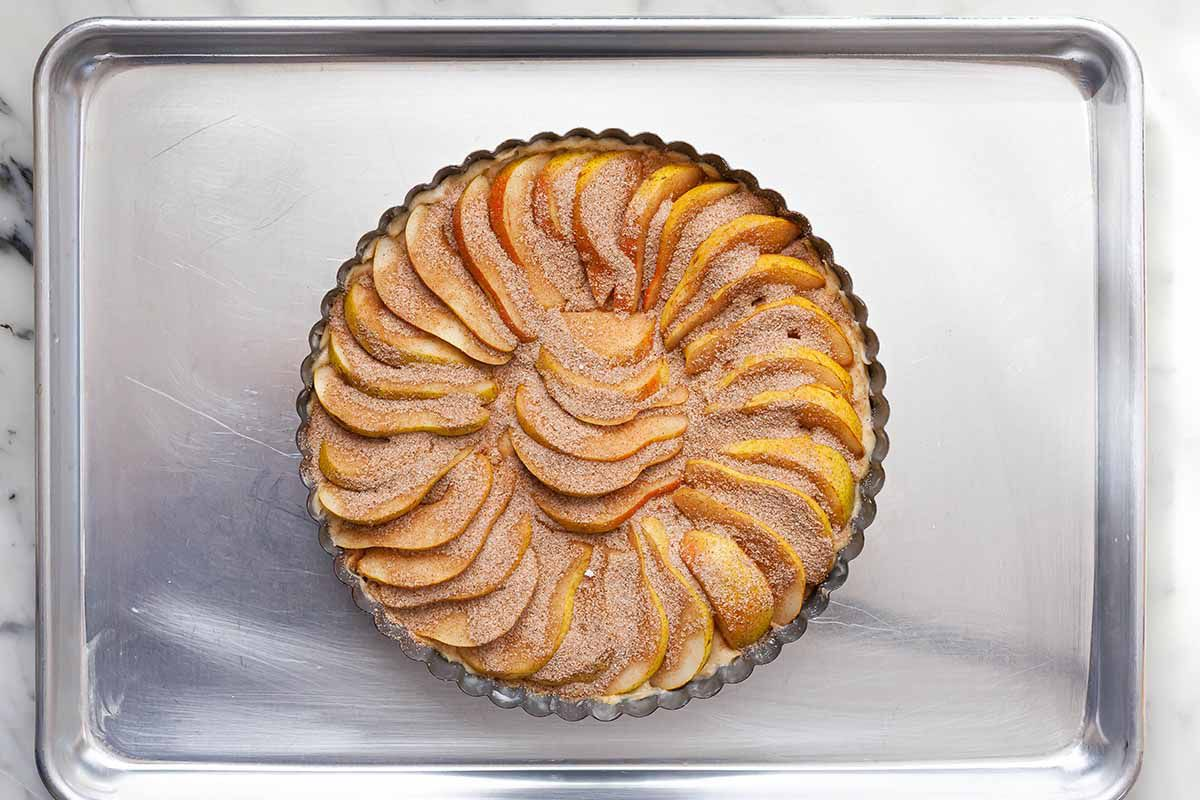 Pear coffee cake in a fluted tart tin dusted with cinnamon and sugar